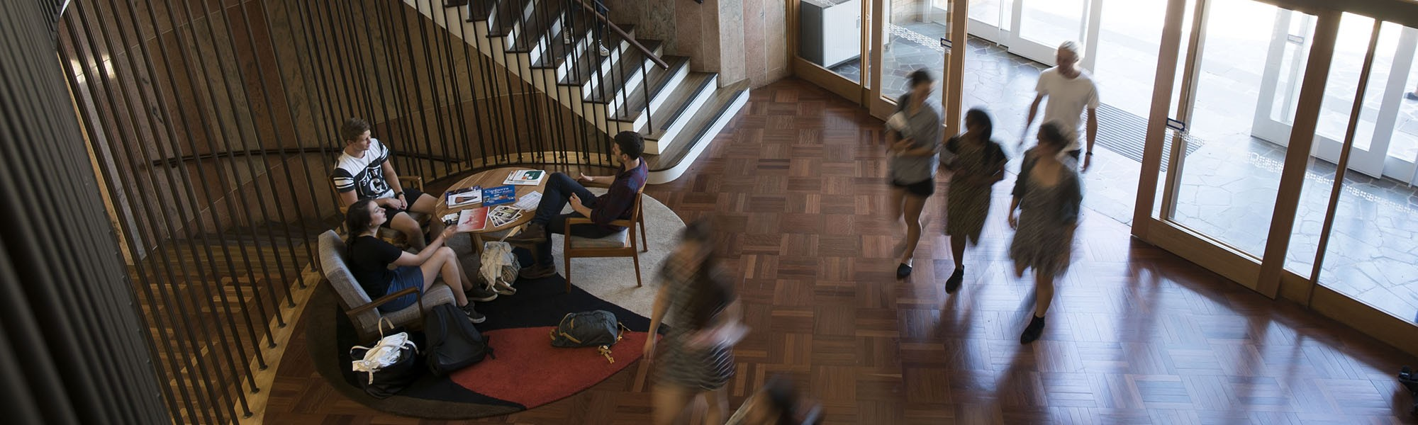 Large foyer with a group of students sitting and talking