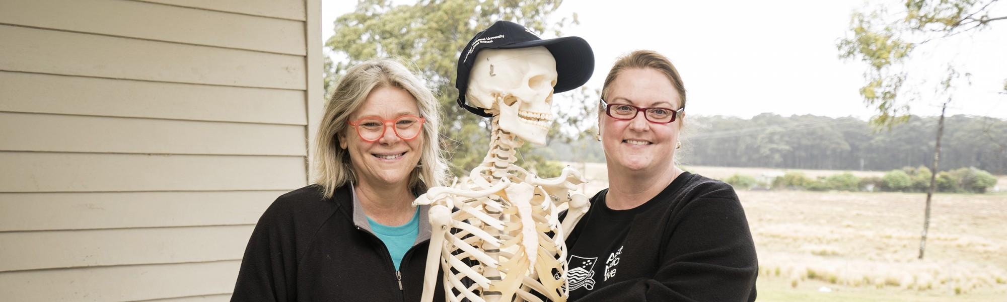 Academics next to teaching skeleton.