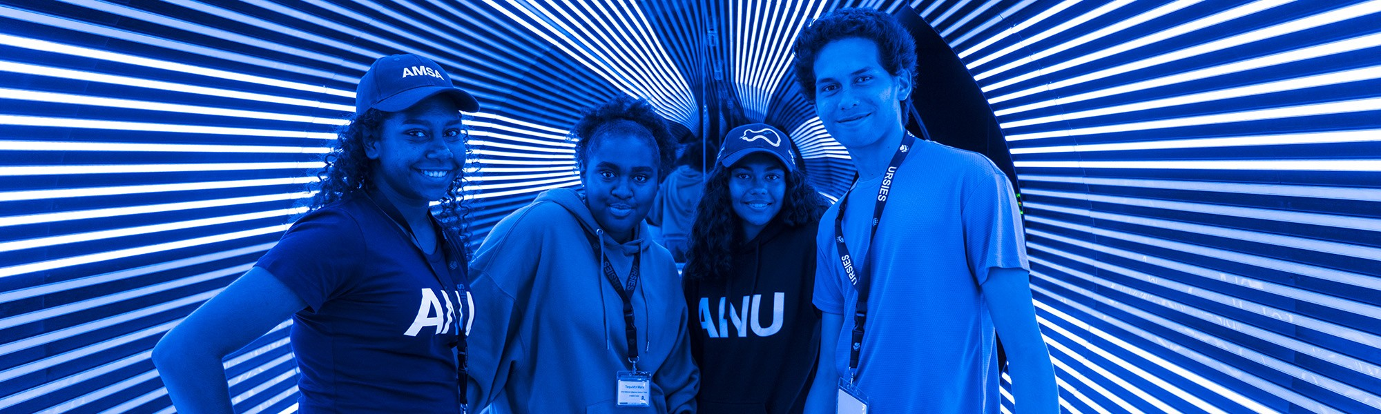 A group of Indigenous Summer Scholars at Questacon tunnel with blue and white lights.