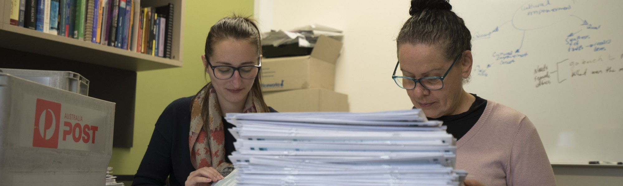 Two researchers sorting through a pile of paper surveys from the Mayi Kuwayu study.