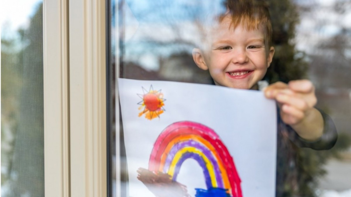 Child in window holding painting