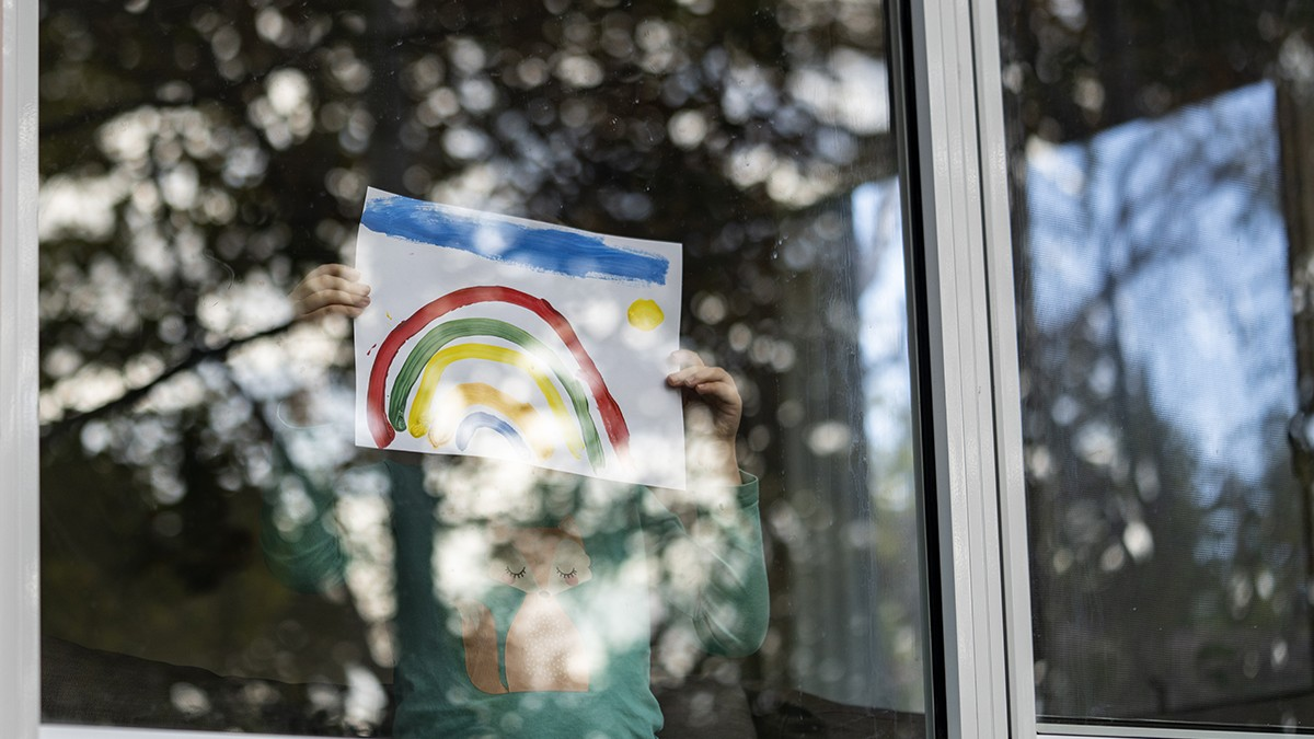 Author's daughter holding a rainbow painting through the window of their home.