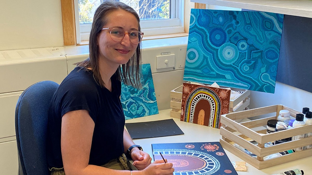 Roxy Jones is sitting at a desk painting Aboriginal artwork, with other canvases around her.