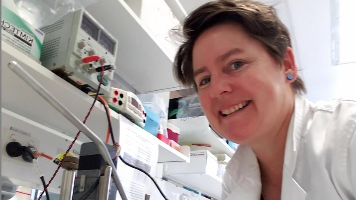 Professor Elizabeth Gardiner smiling in a white lab coat in a laboratory