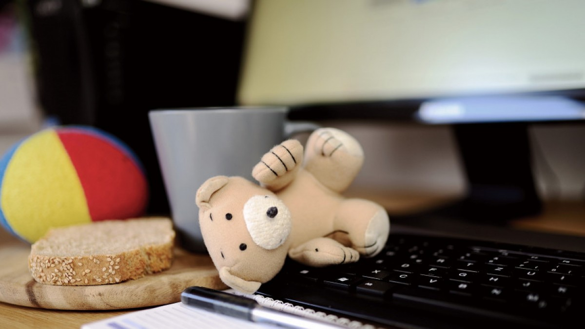 Teddy bear, a slice of bread and ball next to keyboard.