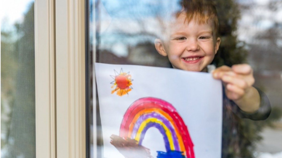 A child holds a picture of a rainbow behind a window.