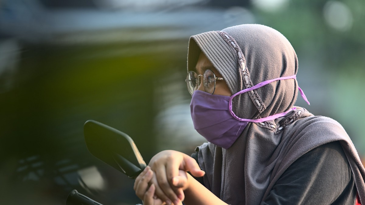 Woman on motorcycle wearing head scarf and mask