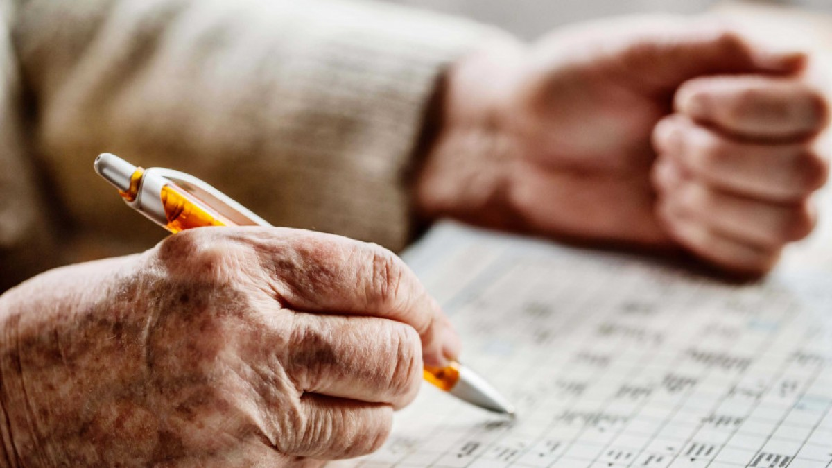 Older person with pen completing Sudoku