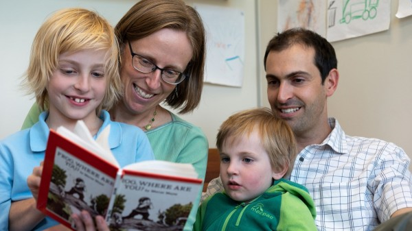 Family reading a children's book together.